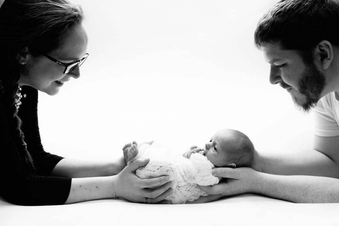 newborn photography baby in parents hands black and white